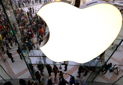 In this Saturday, Oct. 20, 2012, file photo, employees cheer customers as they enter a newly-opened Apple Store in the Wangfujing shopping district in Beijing. (AP Photo/Andy Wong, File)