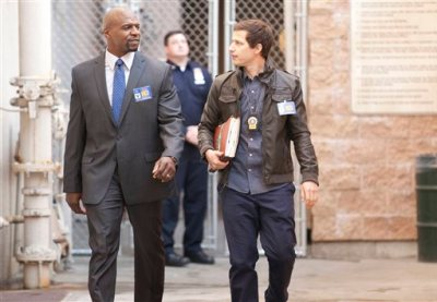 "This image released by Fox shows Terry Crews, left, and Andy Samberg in a scene from ""Brooklyn Nine-Nine."" Fox will break up its Sunday animation block by moving in the critical favorite ""Brooklyn Nine Nine,"" and is replacing two of its Tuesday night comedies with an unscripted show that imagines people setting up a new society in an undeveloped area. (AP Photo/Fox, John Fleenor)"