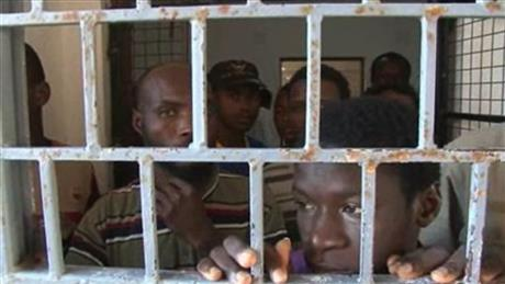 In this image made from Monday, Oct. 14, 2013 video, African migrants look through bars of a locked door at Sabratha migrant detention center for men in Sabratha, Libya. Libya's chaos in the two years following the overthrow of dictator Moammar Gadhafi has turned the country into a prime springboard for tens of thousands of migrants, mainly from Africa, trying to reach Europe in dangerous sea voyages. (AP Photo)