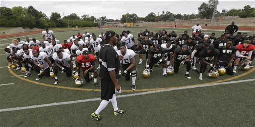 In this Aug. 16, 2013, photo, Alabama State football coach Reggie Barlow talks with his players following practice at the school in Montgomery, Ala. Seventeen of the teams banned by the NCAA for sub-par scores on the newest Academic Progress Rate are in football or men's basketball. Eight of those are historically black colleges including the only two schools to make the list in both sports: Alabama State and Florida A&M. The money gap at Division I colleges is continuing to show up on the playing fields and in the classrooms. Thirty-six teams will be banned from the 2014-15 postseason because of sub-par scores on the newest APR, which was released Wednesday, May 14, 2014. Not one of them comes from a power conference. (AP Photo/Dave Martin)