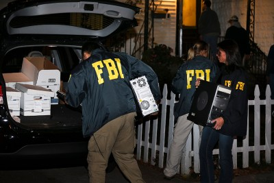 FBI agents remove evidence from the Brooklyn residence of Rabbi Mendel Epstein during an investigation on Oct. 10, 2013, in New York. (AP Photo/John Minchillo)