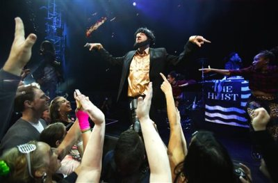 "In this photo taken May 16, 2014, Macklemore of the group Macklemore & Ryan Lewis strikes a pose as he performs ""Thrift Shop"" to a mob of waving fans during Vivid: Spectacle Opening Night Party at the EMP Museum in Seattle. (AP Photo/The Seattle Times, Lindsey Wasson)"