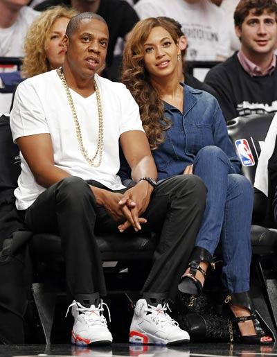 Entrepreneur and singer/songwriter Jay-Z, left, and his wife, singer Beyonce, watch Game 4 of the Brooklyn Nets second-round NBA playoff basketball game against the Miami Heat  at the Barclays Center, Monday, May 12, 2014, in New York. (AP Photo/)