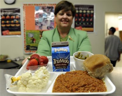 In this Tuesday, April 29, 2014 photo, Becky Domokos-Bays, the director of food and nutrition services at Alexandria City Public Schools, holds up a tray of food during lunch at the Patrick Henry Elementary School in Alexandria, Va. Starting next school year, pasta and other grain products in schools will have to be whole-grain rich, or more than half whole grain. The requirement is part of a government effort to make school lunches and breakfasts healthier. (AP Photo/Susan Walsh)