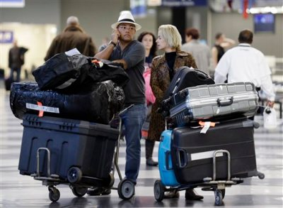 In this Dec. 1, 2013 file photo, travelers walk through terminal 3 baggage claim at O'Hare International airport in Chicago. The government reported Monday, May 5, 2014, that U.S. airlines raised $3.35 billion from bag fees in 2013, down 4 percent from 2012. That's the biggest decline since fees to check a bag or two took off in 2008. (AP Photo/Nam Y. Huh, File)