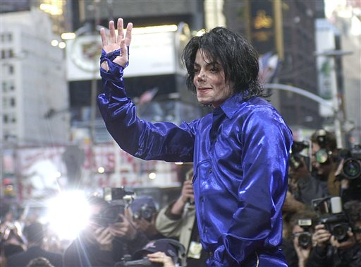 """Nov. 7, 2001 file photo, Michael Jackson waves to crowds gathered to see him at his first ever in-store appearance to celebrate his new album """"Invincible"""" in New York's Times Square.When Michael Jackson's record label released his first posthumous album a year after he passed in 2010, producer Rodney Jerkins was asked to work on the project and he declined. Years later, the hitmaker, who worked heavily on Jackson's 2001 comeback album """"Invincible,"""" says he now feels comfortable producing Jackson music after the King of Pop suddenly died in 2009. He produced the title track from the upcoming album, """"Xscape,"""" out May 13, 2014.  (AP Photo/Suzanne Plunkett, file)"""