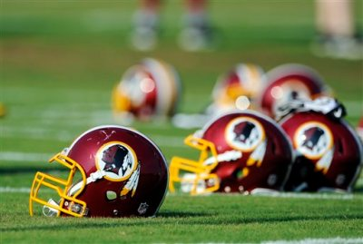 """In this June 17, 2014, file photo, Washington Redskins helmets sit on the field during an NFL football minicamp in Ashburn, Va. The U.S. Patent Office ruled Wednesday, June 18, 2014, that the Washington Redskins nickname is """"disparaging of Native Americans"""" and that the team's federal trademarks for the name must be canceled. The ruling comes after a campaign to change the name has gained momentum over the past year. (AP Photo/Nick Wass, File)"""