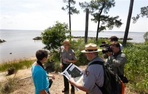 United States Interior Secretary Sally Jewell, left, looks over recovered artifacts as she listens to curator Melanie Pereira, right, during a tour of Jamestown Island in Jamestown, Va., Thursday, June 5, 2014. Jewell toured Jamestown to highlight climate change's threat to the first permanent European settlement in America. The island settled in 1607 is among the coastal Virginia lands being lost to rising seas.    (AP Photo/Steve Helber)