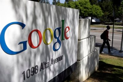 In this June 5, 2014 photo, a man walks past a Google sign at the company's headquarters in Mountain View, Calif. Google is buying Skybox Imaging in a deal that could serve as a launching pad for the Internet company to send its own fleet of satellites to take aerial pictures and provide online access to remote areas of the world. (AP Photo/Marcio Jose Sanchez)