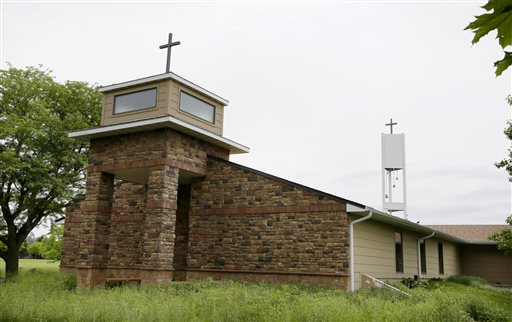 In this June 10, 2014 photo a cellphone tower inside the bell tower, rear right, is seen over the Resurrection Lutheran Church in Ankeny, Iowa. As wireless companies fill gaps in their networks, many have sought to camouflage the ungainly outdoor equipment that carries the nation's daily diet of calls, text messages and data. (AP Photo/Charlie Neibergall)
