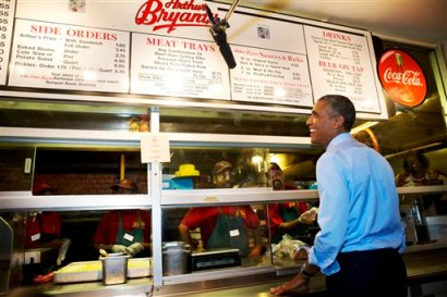 President Barack Obama orders barbecue at Arthur Bryant's Barbeque restaurant in Kansas City, Mo., Tuesday, July 29, 2014, before meeting with four Kansas City residents who wrote him letters, over dinner a. According to the White House the Kansas City letter writers include a man who thanked Obama for student loan help he received, a single mother who described her challenges raising children and running a business, a teacher in a GED program and a woman who is active in her neighborhood association. (AP Photo/Jacquelyn Martin)