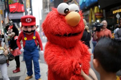 """A person dressed as Elmo shakes hands with a pedestrian in Times Square on Monday, July 28, 2014 in New York. New York City Mayor Bill de Blasio said Monday that he believes the people wearing character costumes in Times Square should be licensed and regulated. Dozens of people dressed as kids' favorites like Elmo, Cookie Monster and Batman stand near 42nd Street and pose for photos with tourists in exchange for money. De Blasio said the practice has """"gone too far.""""  A man dressed as Spider-man was arrested Saturday, July 28, 2014, after punching a police officer who told him to stop harassing tourists.  The City Council is working on legislation that would require the characters to get a city-approved license.  (AP Photo/Seth Wenig)"""
