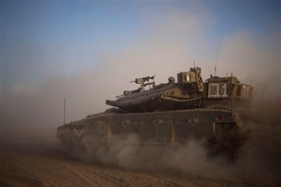 An Israeli tank maneuvers to take a position along the Israel-Gaza Border, Thursday, July 17, 2014. Israel and Hamas have begun observing a five-hour humanitarian cease-fire, as fighting extended into a 10th day. The two sides agreed to the pause following a request by the United Nations so that supplies could be delivered to Gaza.(AP Photo/Ariel Schalit)