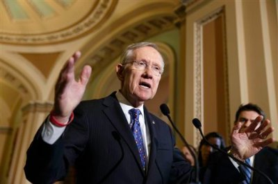 This June 3, 2014, file photo shows  Senate Majority Leader Harry Reid of Nev., as he speaks to reporters on Capitol Hill in Washington. The Senate voted to advance an election-year bill limiting tax breaks for U.S. companies that move operations overseas. But big hurdles remain. (AP Photo/J. Scott Applewhite, File)