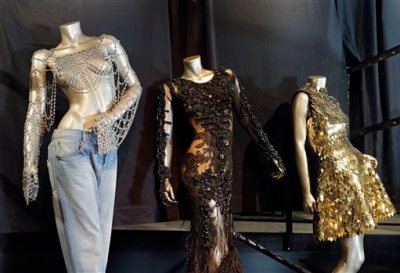 """In this Thursday, July 17, 2014 photo, from left, outfits from Beyonce's 2003 """"Dangerously in Love,"""" 2012 """"Met Gala"""" and 2011 """"Run the World (Girls)"""" are shown in a new exhibit at the Rock and Roll Hall of Fame in Cleveland. The Rock Hall announced Friday, July 18, 2014, that outfits from Beyonce's Super Bowl performance and music videos will debut Tuesday in the Ahmet Ertegun Main Exhibit Hall in its Legends of Rock section next to iconic pieces from Michael Jackson, David Bowie and Bruce Springsteen. (AP Photo/Mark Duncan)"""