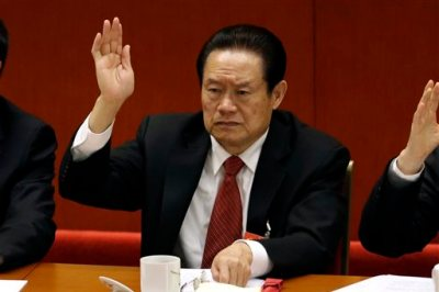 In this photo taken Wednesday Nov. 14, 2012, Zhou Yongkang, then Chinese Communist Party Politburo Standing Committee member in charge of security, raises his hand to show approval for a work report during the closing ceremony for the 18th Communist Party Congress at the Great Hall of the People in Beijing, China. China's ruling Communist Party  announced Tuesday, July 29, 2014 an investigation into the former security chief, a move that usually paves the way for criminal prosecution.  (AP Photo/Lee Jin-man)