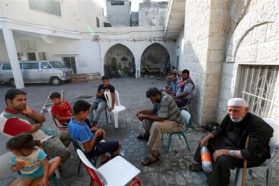 Palestinians sit on the grounds of the St. Porphyrios Church in Gaza City, Wednesday, July 23, 2014. St. Porphyrios Church has thrown its doors open to hundreds of displaced Palestinians. (AP Photo/Lefteris Pitarakis)