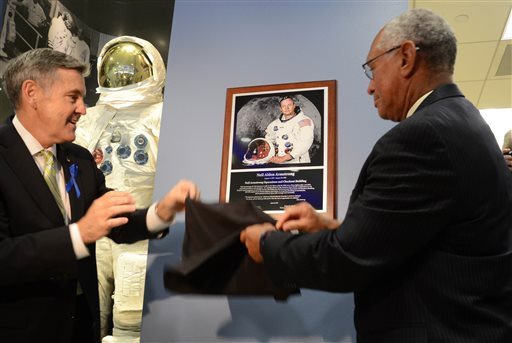 Kennedy Space Center Director Robert Cabana, left, and NASA Administrator Charles Bolden unveil a plaque of astronaut Neil Armstrong,  the first man to walk on the moon, in the Operations and Checkout building at Kennedy Space Center, Fla., during a ceremony to rename the building in Armstrong's honor, Monday, July 21, 2014. The building was renamed for Apollo astronaut Neil Armstrong.  (AP Photo, Florida Today, Craig Bailey)