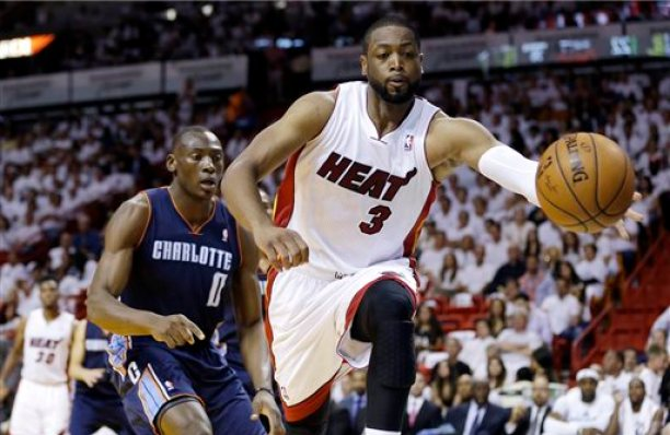 """In this April 20, 2014, file photo, Miami Heat's Dwyane Wade (3) grabs a ball from going out of bounds as Charlotte Bobcats' Bismack Biyombo (0) defends during the first half in Game 1 of an opening-round NBA basketball playoff series in Miami.  A person familiar with the situation says Wade is staying with the Heat, agreeing to a two-year deal with a player option for 2015-16. Wade made reference to the deal Tuesday, Kuly 15, 2014, tweeting """"Home Is Where the Heart Is"""" and calling himself a """"HeatLifer"""" in a photo of him below Miami's three NBA championship banners. (AP Photo/Lynne Sladky, File)"""