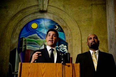 Denver City Attorney Scott Martinez, left, and Qusair Mohamedbhai, representing Jamal Hunter, give a news conference in Denver on Tuesday, July 22, 2014 about a settlement reached by both sides in the amount of $3.25 million. The federal jail-abuse lawsuit was filed by Hunter, a former inmate who said a deputy ignored his screams while a group of fellow inmates brutally beat him and scalded his genitals with hot water. (AP Photo/The Denver Post, AAron Ontiveroz)