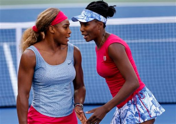 Serena Williams, left, and Venus Williams talk between points against Timea Babos and Kristina Mladenovic during a doubles match at the 2014 U.S. Open tennis tournament, Thursday, Aug. 28, 2014, in New York. (AP Photo/Matt Rourke)