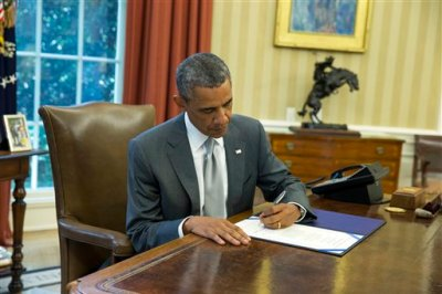 "President Barack Obama signs ""H.J. Res. 76,"" a bill that provides an additional $225 million in U.S. taxpayer dollars for Israel's Iron Dome missile defense system, in the Oval Office of the White House, Monday, Aug. 4, 2014, in Washington. (AP Photo/ Evan Vucci)"