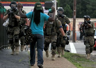 Police wearing riot gear point their weapons before arresting a man Aug. 11, 2014, in Ferguson, Mo. (Jeff Roberson/AP Photo)