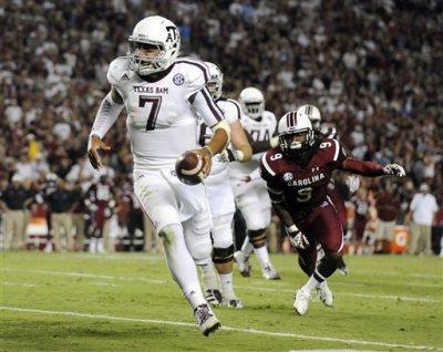 Texas A&M quarterback Kenny Hill (7) runs as South Carolina linebacker Sharrod Golightly (9) defends during the second half of an NCAA college football game on Thursday, Aug. 28, 2014, in Columbia, S.C. (AP Photo/Rainier Ehrhardt)