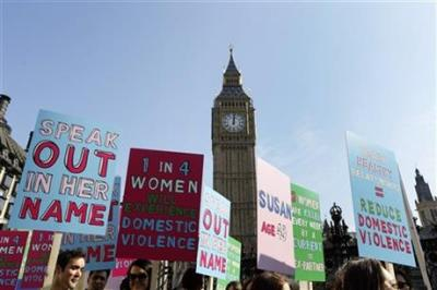 In this Tuesday, March 5, 2013 file photo people hold banners during a demonstration against domestic violence near Big Ben in London, in the lead up to International Women's Day. About a third of women worldwide have been physically or sexually assaulted by a former or current partner, according to the first major review of violence against women. In a series of papers released on Thursday June 20, 2013 by the World Health Organization and others, experts estimated nearly 40 percent of women killed worldwide were slain by an intimate partner and that being assaulted by a partner was the most common kind of violence experienced by women. (AP Photo/Kirsty Wigglesworth, File)