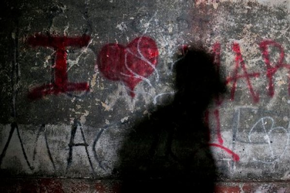 In this Aug. 26, 2014 photo, the shadow of a migrant is seen on the wall of a train depot in the town of Chahuites, Mexico, which has decided to protect and aid migrants passing through. Town officials say they do not allow federal police raids on migrants to happen in their small municipality. Local police, tasked with protecting migrants passing through town, stood watch along the tracks near migrants resting and sleeping outdoors. (AP Photo/Rebecca Blackwell)