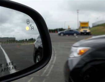 This file photo shows a demonstration of a side mirror warning signal in a Ford Taurus at an automobile testing area in Oxon Hill, Md. (AP Photo/Susan Walsh, File)