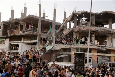 Palestinians attend a victory rally organized by masked militant of Izzedine al-Qassam Brigades, military wing of Hamas, at the debris of destroyed houses in Shijaiyah, neighborhood of Gaza City, in the northern Gaza Strip, Wednesday, Aug. 27, 2014. An open-ended cease-fire between Israel and Palestinian militants in the Gaza Strip was holding Wednesday. (AP Photo/Adel Hana)