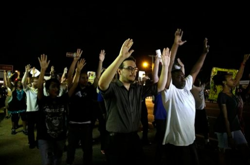 Protesters march down the street in Ferguson, Mo. Tuesday, Aug. 19, 2014. On Saturday, Aug. 9, 2014, a white police officer fatally shot Michael Brown, an unarmed black teenager, in the St. Louis suburb. (AP Photo/Jeff Roberson)