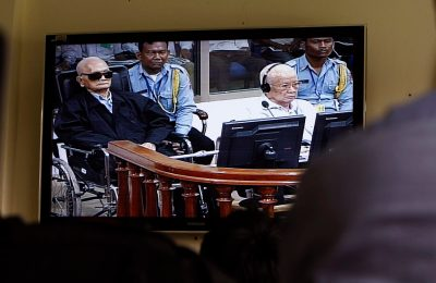 Khieu Samphan, second from right, former Khmer Rouge head of state, and Noun Chea, left, who was the Khmer Rouge's chief ideologist and No. 2 leader, is seen on a screen at the court's press center of the U.N.-backed war crimes tribunal in Phnom Penh, Cambodia, Thurdday, Aug. 7, 2014. Three and a half decades after the genocidal rule of Cambodia's Khmer Rouge ended, a U.N.-backed war crimes tribunal is due to deliver its first verdicts Thursday in a historic case against the only two leaders of the regime left to stand trial. (AP Photo/Heng Sinith)