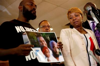 Lesley McSpadden, right, the mother of 18-year-old Michael Brown, watches as Brown's father, Michael Brown Sr., holds up a family picture of himself, his son, top left in photo, and a young child during a news conference Monday, Aug. 11, 2014, in Ferguson, Mo. Michael Brown, 18, was shot and killed in a confrontation with police in the St. Louis suburb of Ferguson, Mo, on Saturday, Aug. 9, 2014. (AP Photo/Jeff Roberson)