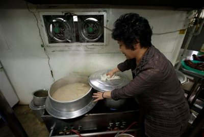 In this photo taken on Tuesday, Aug. 12, 2014, a chef and owner Oh Keum-il of Daegyo, the dog meat restaurant, shows how to cook for dog meat at her restaurant in Seoul, South Korea. Daegyo, the famous dog meat restaurant she opened in a Seoul alley in 1981, will serve its last bowl of boshintang, or dog stew, on Friday, a reflection of the challenges facing a trade that is neither legal nor explicitly banned under South Korean laws governing livestock and food processing. (AP Photo/Lee Jin-man)