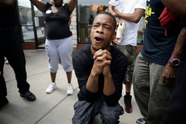 A man bends down in prayer as police try to disperse a small group of protesters Monday, Aug. 18, 2014, in Ferguson, Mo. The Aug. 9 shooting of Michael Brown by police has touched off rancorous protests in Ferguson, a St. Louis suburb where police have used riot gear and tear gas. Gov. Jay Nixon ordered the National Guard to help restore order Monday, while lifting a midnight-to-5 a.m. curfew that had been in place for two days. (AP Photo/Jeff Roberson)