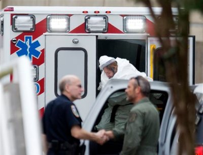 A person wearing a haz-mat suit steps out of an ambulance as an ebola patient arrives for treatment, Tuesday, Sept. 9, 2014, in Atlanta. The fourth American aid worker sickened with the Ebola virus arrived Tuesday morning for treatment at Emory University Hospital, where two others have been successfully treated. (AP Photo/David Goldman)