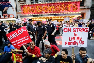Protesters sit in front of a McDonald's restaurant on 42nd Street in New York's Times Square as police officers move in to begin making arrests, Thursday, Sept. 4, 2014. The protesters are seeking to get pay increases to $15 per hour. Thursday's demonstration is part of a day of planned protests in 150 cities across the country by workers from fast-food chains. (AP Photo/Mark Lennihan)