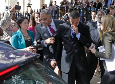Former Charlotte Mayor Patrick Cannon, center right, leaves the federal courthouse in Charlotte, N.C., Tuesday, Oct. 14, 2014, after being sentenced to 44 months in prison. In a deal with prosecutors, Cannon pleaded guilty in June to one count of honest services wire fraud. Prosecutors say Cannon accepted nearly $50,000 in bribes between January 2013, when he was a city councilman, and February 2014, three months after he was elected mayor. (AP Photo/Chuck Burton)