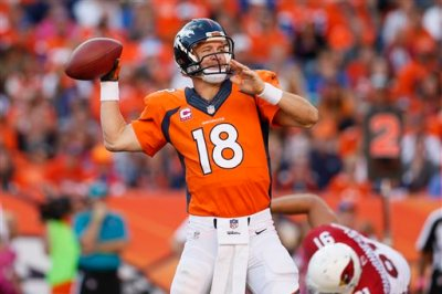 In this Oct. 5, 2014, file photo, Denver Broncos quarterback Peyton Manning (18) throws against the Arizona Cardinals during the second half of an NFL football game, in Denver. The Broncos won 41-20. Brett Favre says he couldn't be happier to see Peyton Manning on the brink of breaking his own NFL record of 508 touchdown throws. Manning has 503 heading into Denver's road game Sunday Oct. 12 against the New York Jets. (AP Photo/Joe Mahoney, File)