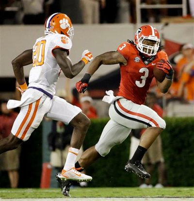 In this Aug. 30, 2014, file photo, Georgia's Todd Gurley, right, runs the ball past Clemson's Jayron Kearse in the second half of an NCAA college football game in Athens, Ga. Georgia will file a request with the NCAA for Gurley's eligibility to be reinstated. Gurley has been suspended for the last two games while Georgia investigated allegations he broke NCAA rules by receiving improper benefits. (AP Photo/David Goldman, File)
