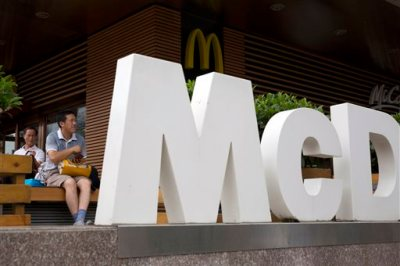 In this July 22, 2014 file photo, a man rests outside a McDonald's restaurant in Beijing. McDonald's reports quarterly financial results on Tuesday, Oct. 21, 2014. (AP Photo/Ng Han Guan, File)