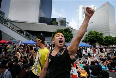 A pro-democracy activist shouts slogans on a street near the government headquarters where protesters have made camp, Wednesday, Oct. 1, 2014 in Hong Kong. Holiday crowds swelled into the tens of thousands as student leaders met with other pro-democracy protesters Wednesday to thrash out a strategy for handling the government's rejection of their demands that the city's top leader resign and Beijing revise its plans to limit political reforms. (AP Photo/Wong Maye-E)