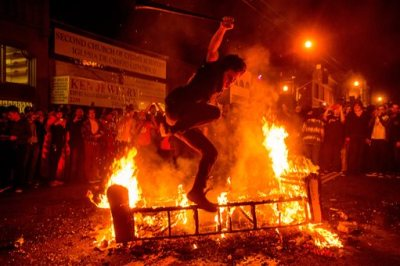 A man jumps over a burning couch in the Mission district after the San Francisco Giants beat the Kansas City Royals to win the World Series on Wednesday, Oct. 29, 2014, in San Francisco. (AP Photo/Noah Berger)