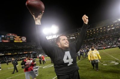 Oakland Raiders quarterback Derek Carr (4) celebrates after the Raiders defeated the Kansas City Chiefs 24-20 in an NFL football game in Oakland, Calif., Thursday, Nov. 20, 2014. (AP Photo/Marcio Jose Sanchez)