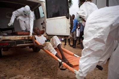 In this file photo taken on Wednesday, Sept. 24, 2014,  healthcare workers load a man, center, onto a ambulance as he is  suspected of suffering from the Ebola virus in Kenema, Sierra Leone. A doctor in Sierra Leone has died of Ebola — the fifth local doctor in the West African nation to die of the disease, authorities said Monday, Nov. 3, 2014. (AP Photo/Tanya Bindra, File)