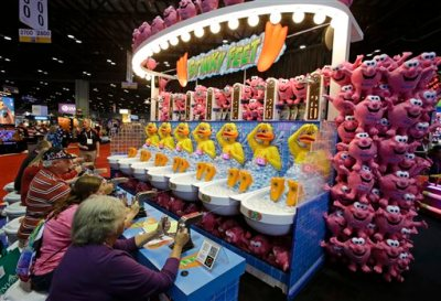 """In this Tuesday, Nov. 18, 2014 file photo, trade show attendees compete at a water game called Stinky Feet at the International Association of Amusement Parks and Attractions convention and trade show in Orlando, Fla. The annual International Association of Amusement Parks and Attractions Expo is a massive industry trade show. the real buzzword at the show is """"interactivity."""" It seems that every vendor and park owner is seeking to somehow merge thrill rides with video games. (AP Photo/John Raoux, File)"""