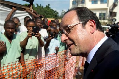 French President Francois Hollande is welcomed by members of the NGO MSF (Doctors without borders), upon his arrival at Donka hospital in Conakry, Guinea, Friday, Nov. 28, 2014. Hollande is visiting the Ebola stricken country during a seven-hour stop on his way to Dakar, Senegal. (AP Photo/Alain Jocard, Pool)