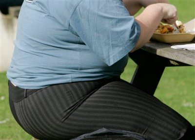 This is a Wednesday, Oct. 17, 2007  file photo of an overweight person  eating in London.  A new report by the McKinsey Global Institute released Thursday  Nov. 20, 2014 that the global cost of obesity has risen to $2 trillion annually — nearly as much as smoking or the combined impact of armed violence, war and terrorism. The report released Thursday focused on the economics of obesity, putting it among the top three social programs generated by human beings. It puts its impact at 2.8 percent of global gross domestic product.  (AP Photo/Kirsty Wigglesworth, File)